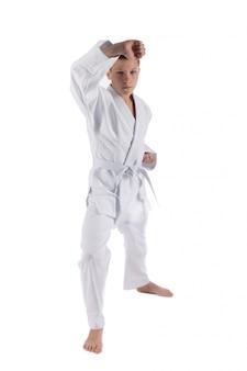 Rapaz posando com técnicas de karatê em branco isolado