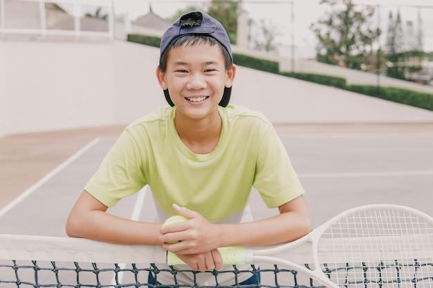 Rapaz pré-adolescente asiático jogando tênis, treinamento de jovens atletas saudáveis, conceito de bem-estar ativo