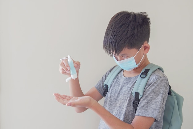 Rapaz pré-adolescente asiático misto usando máscara e aplicando desinfetante para as mãos, de volta ao conceito de escola