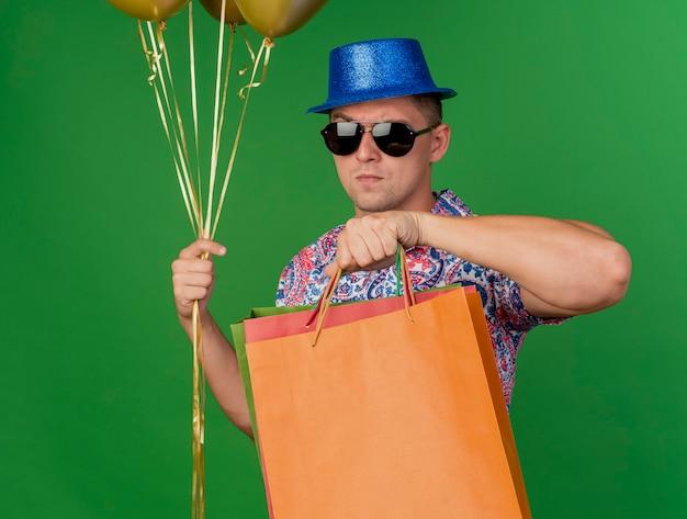 Rapaz rigoroso e festeiro com chapéu azul e óculos, segurando balões com sacolas de presente isoladas no verde