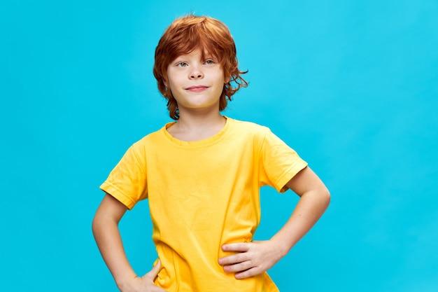 Rapaz ruivo com as mãos na cintura em um fundo azul