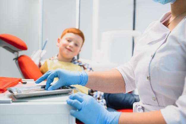 Rapaz satisfeito com o atendimento no consultório odontológico. conceito de tratamento odontológico pediátrico