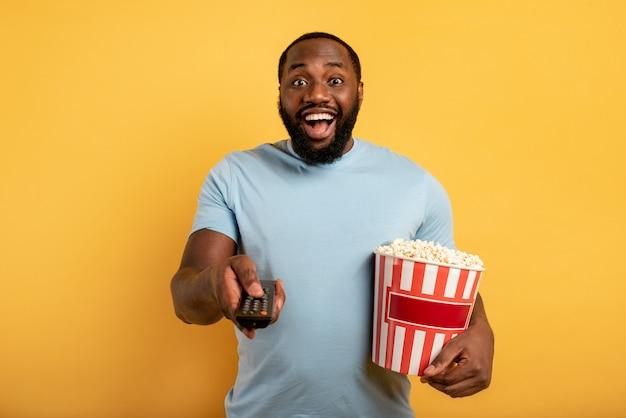 Rapaz se diverte assistindo a um filme. conceito de entretenimento e streaming de tv. fundo vermelho