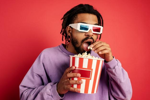 Rapaz se diverte assistindo a um filme. conceito de entretenimento e streaming de tv. parede vermelha