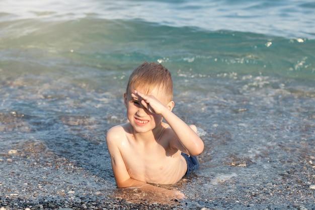 Rapaz se divertindo nas ondas do mar ou oceano em um dia ensolarado de verão. costa do oceano e praia. estilo de vida ativo e conceito de recreação.