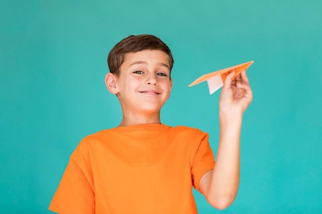 Rapaz se preparando para lançar um avião de papel