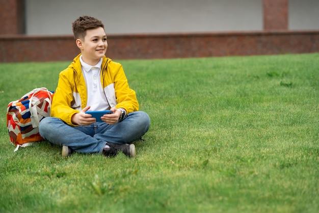 Rapaz se senta no gramado com um telefone inteligente nas mãos.