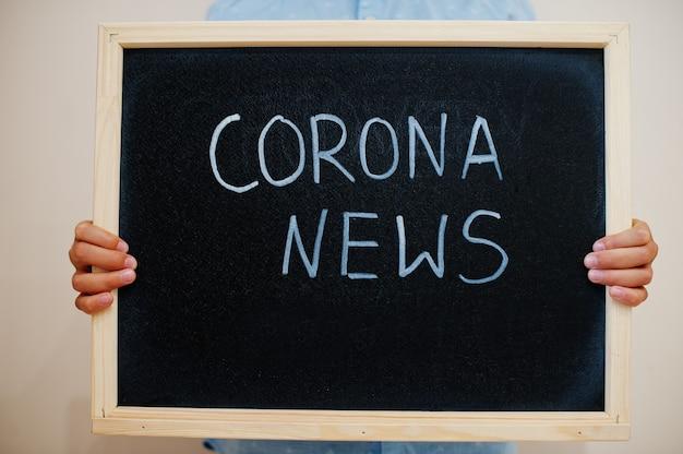 Rapaz segura inscrição no quadro com o texto notícias da corona