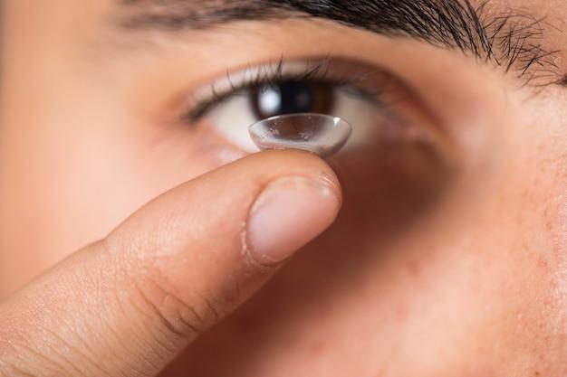 Rapaz segurando uma lente no dedo