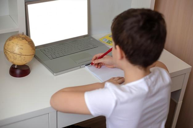 Rapaz senta-se de costas atrás de um laptop, olha para o monitor.
