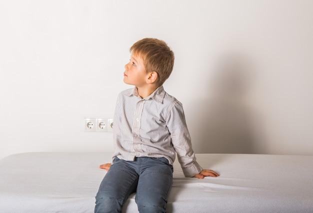 Rapaz senta-se no sofá médico no quarto