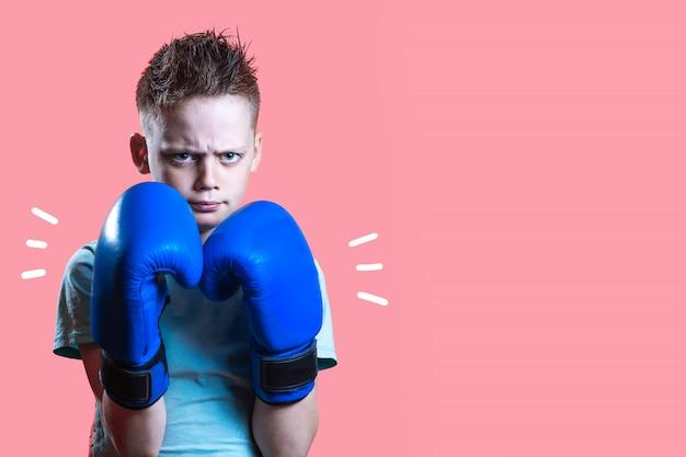 Rapaz severo em luvas de boxe azuis em amarelo brilhante