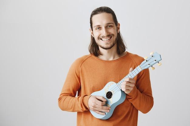 Rapaz sorridente alegre e moderno com ukulele