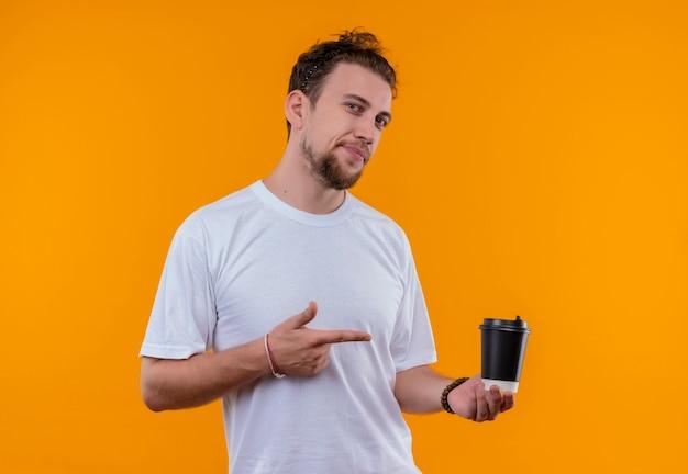 Rapaz sorridente, vestindo uma camiseta branca, aponta para uma xícara de café na mão em um fundo laranja isolado