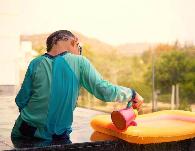 Rapaz, sozinho, joga água derramando na beira da piscina na piscina com luz do sol nas férias de verão