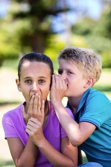 Rapaz sussurrando no ouvido da irmã