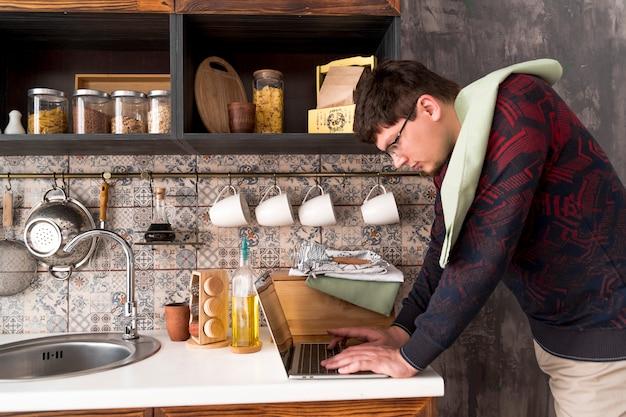 Rapaz trabalhando no laptop cinza