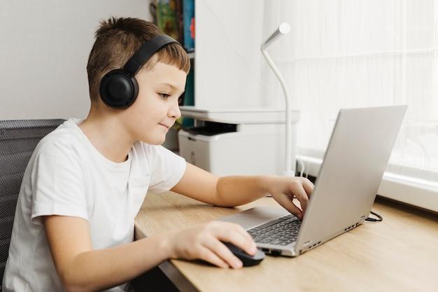 Rapaz, uma casa usando laptop e fones de ouvido