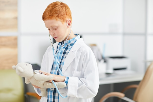Rapaz vestindo jaleco branco e brincando de médico