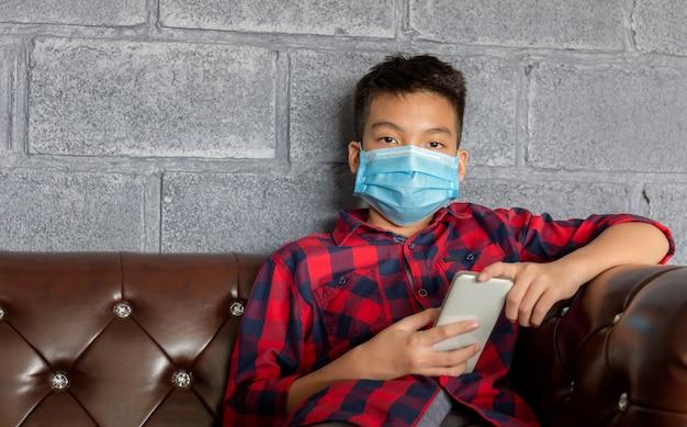 Rapaz vestindo uma máscara protetora e segurando um smartphone