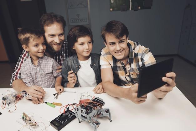 Rapazes adolescente e um homem adulto fazem selfie em um tablet preto