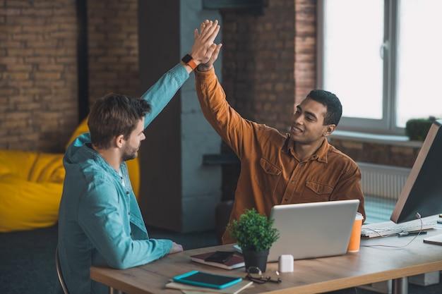 Rapazes agradáveis se cumprimentando enquanto trabalham juntos