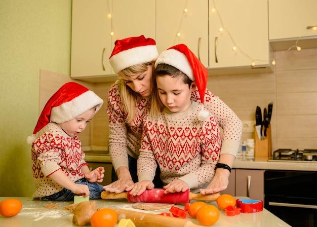 Rapazes alegres e mãe cozinhando biscoitos de natal em casa. mãe e filhos fazendo casa de pão de gengibre.