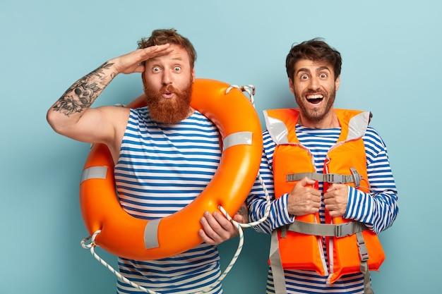 Rapazes alegres posando na praia com colete salva-vidas e bóia salva-vidas