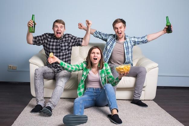 Rapazes bebem cerveja, comem pizza e torcem pelo futebol