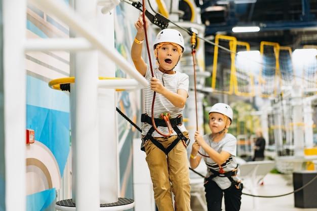 Rapazes caucasianos de 7-8 anos de idade escalando no parque aventura, passando por uma pista de obstáculos. parque de corda alta dentro de casa. foto de alta qualidade