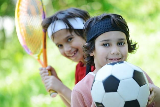 Rapazes com futebol e tênis fora