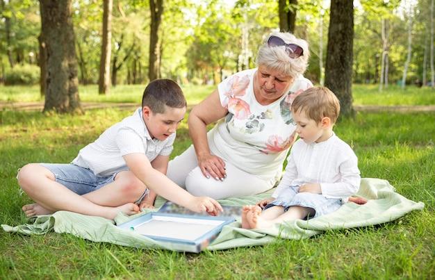 Rapazes e avó sentada no parque ensolarado de verão.