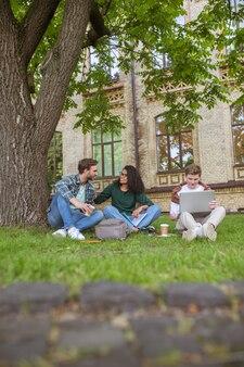 Rapazes e uma menina sentados na grama perto do prédio da faculdade