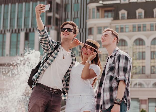 Rapazes elegantes posam para uma selfie perto de uma fonte