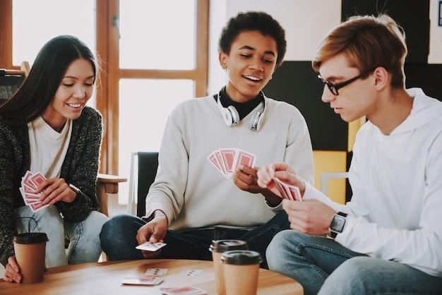 Rapazes engraçados jogam cartas em casa juntos.