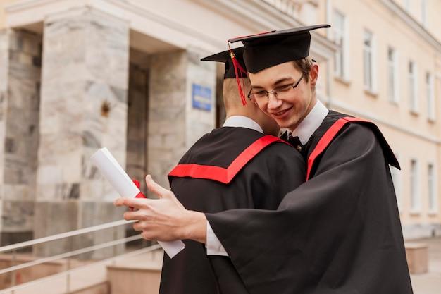 Rapazes graduados abraçando