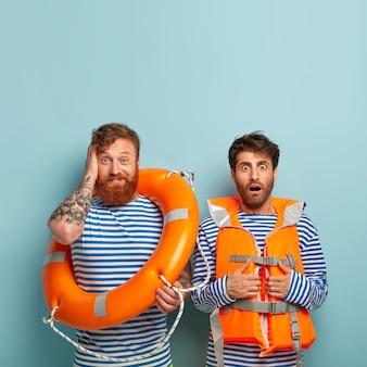 Rapazes horrorizados posando na praia com colete salva-vidas e bóia salva-vidas