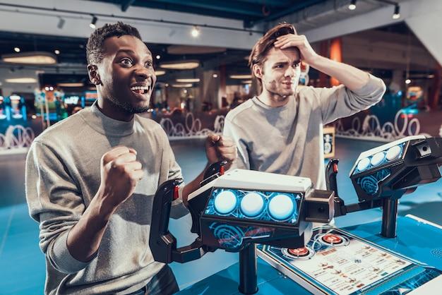 Rapazes jogam jogos na sala de jogos.