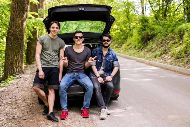 Rapazes jovens alegres sentado no porta-malas na estrada da floresta