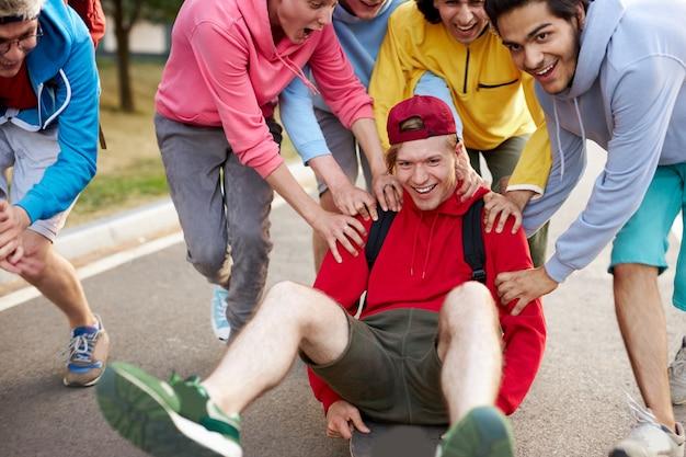 Rapazes modernos e amigáveis em roupas casuais andando de skate