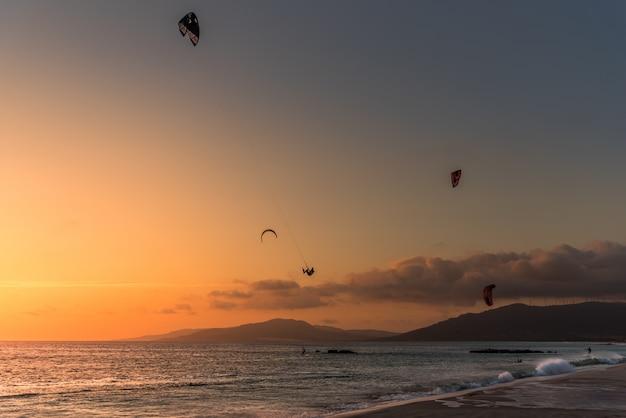 Rapazes praticando kite surf na praia de cádiz, espanha