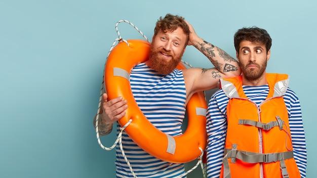 Rapazes satisfeitos posando na praia com colete salva-vidas e bóia salva-vidas
