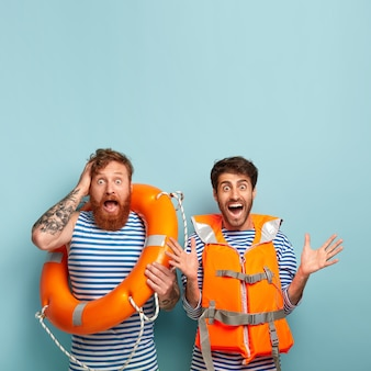 Rapazes superemotivos animados posando na praia com colete salva-vidas e bóia salva-vidas