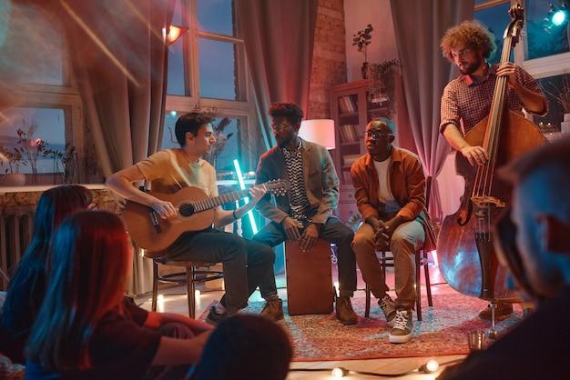 Rapazes tocando instrumentos musicais se apresentando para seus fãs no estúdio