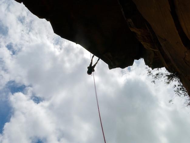 Rapel em uma parede de pedra sanstone negativa com céu azul - vista de baixo