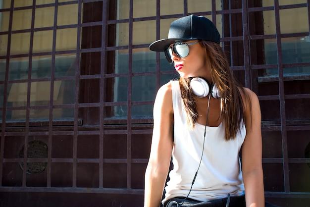 Rapper garota com fones de ouvido em uma cidade europeia