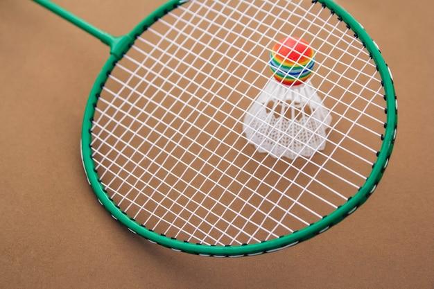 Raquete de badminton e peteca em um fundo marrom e copie o espaço.