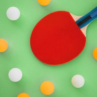 Raquete de ping-pong vermelho com bolas brancas e laranja em fundo verde