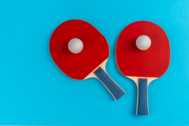 Raquete de ping pong vermelho sobre um fundo azul