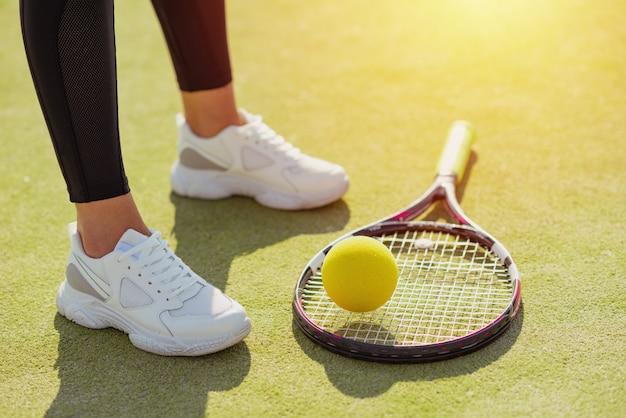 Raquete de tênis, bola e pernas femininas em tênis esporte na quadra close-up